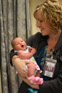 Emmy Davis, Certified Nurse Midwife, preparing one of the little ones to go home!